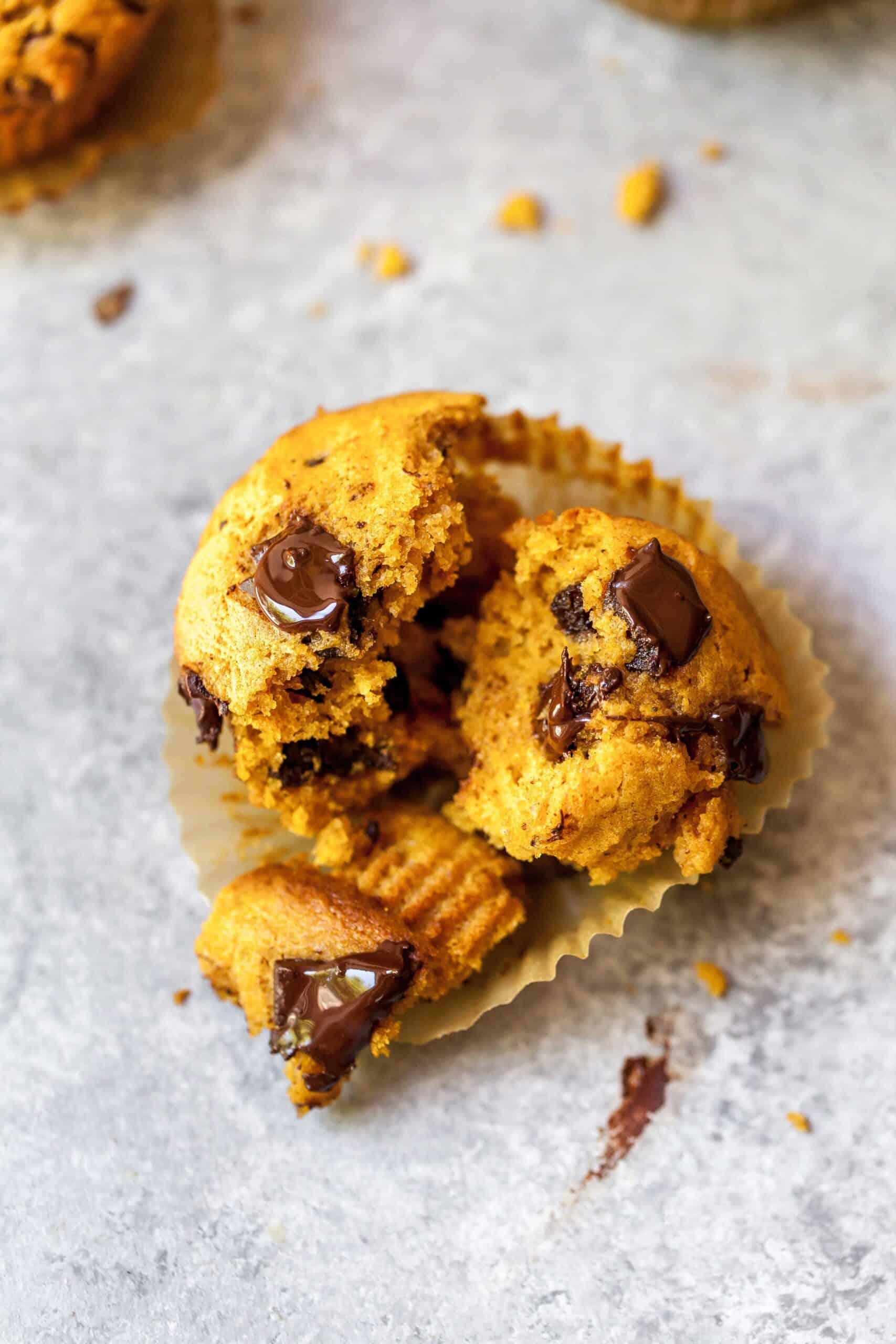 Closeup shot of a pumpkin spice chocolate chunk muffin broken into pieces