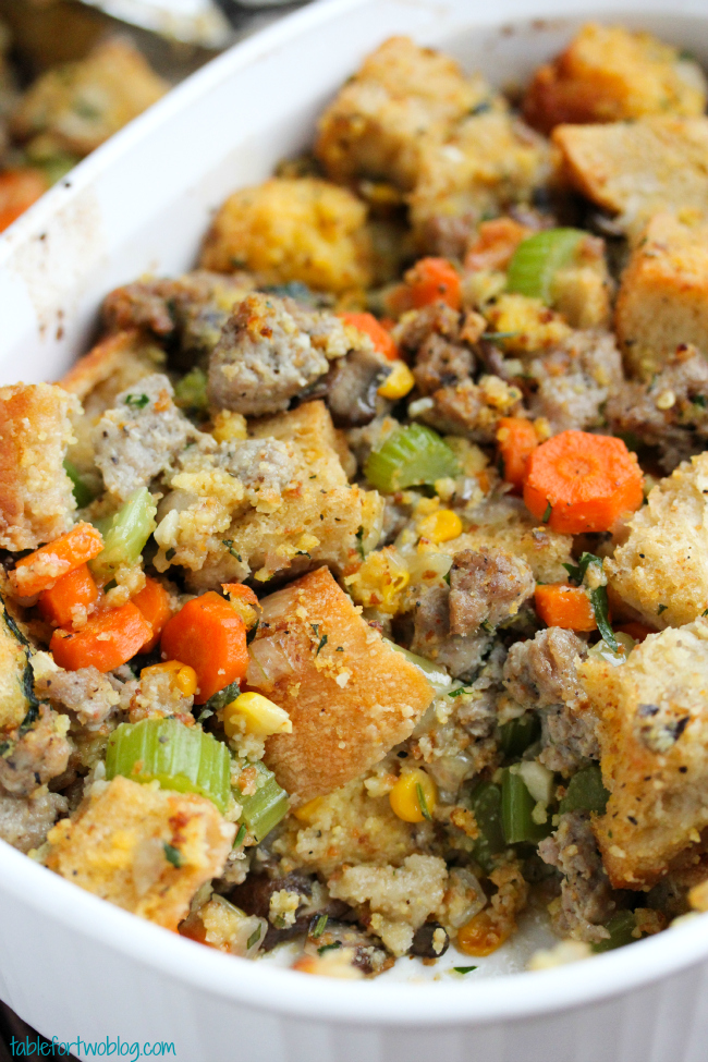 Closeup of cornbread and sausage stuffing in white oval baking dish