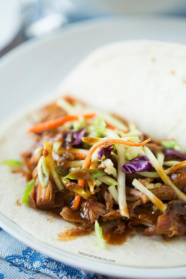 Slow cooker Korean tacos are so easy to make and the results are a tender & flavorful pork wrapped inside a warm tortilla and topped with a tangy slaw!