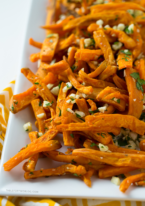 These baked garlic sweet potato fries are a great side dish for any burger or whenever the craving hits! Recipe on tablefortwoblog.com