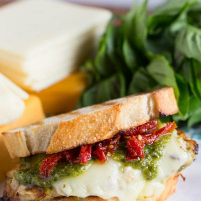 A bold and cheesy pesto chicken sandwich with sundried tomatoes!