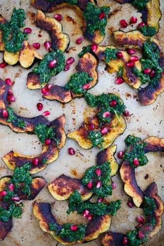 Roasted acorn squash with arugula pesto and pomegranate is a great side dish addition to any meal! You'll love how vibrant and colorful this side dish looks on your table!