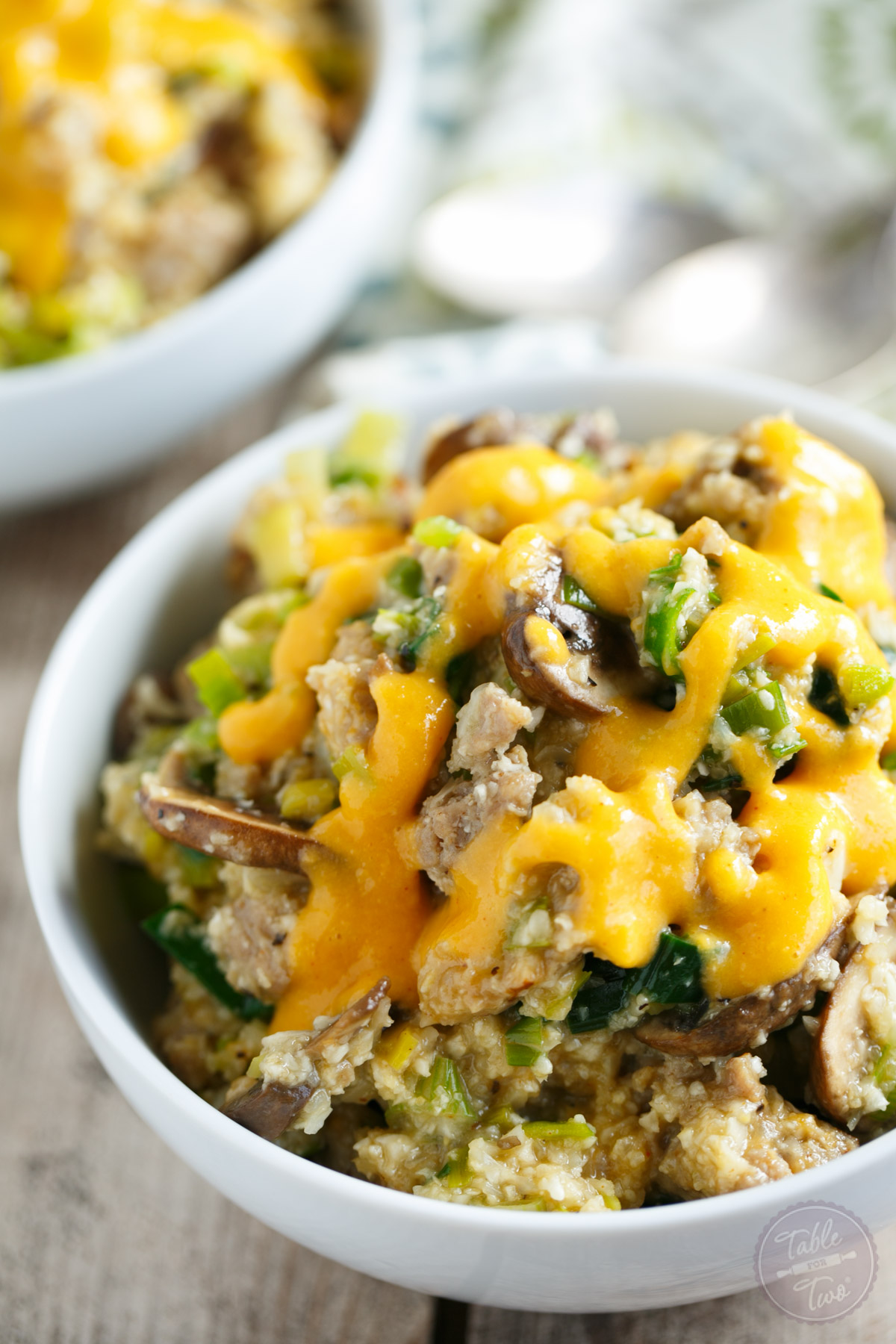 A cauliflower bowl with mushrooms, leeks, and brats topped with a beer-cheese sauce made with Sargento Extra Sharp Cheddar! #sponsored