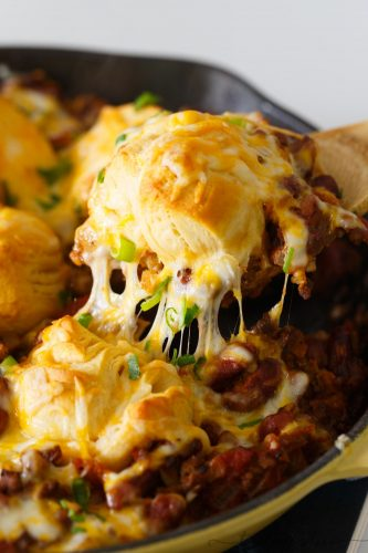 Pure comfort food is right here. Frito pie chili biscuit skillet has your name written all over it if you are looking for something that will stick to your ribs! Chili topped with fritos, cheese, and biscuits — what more could you ask for?!