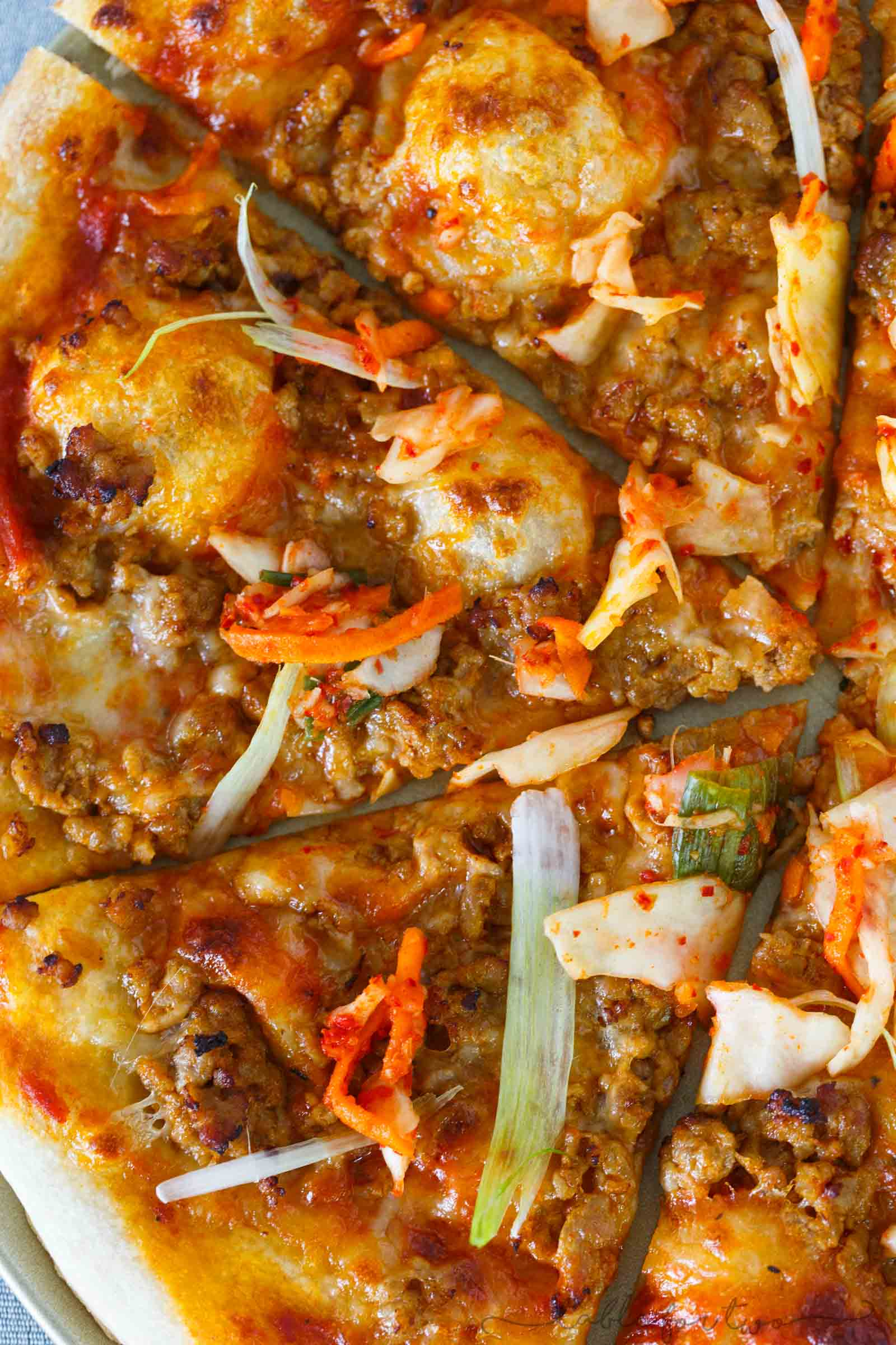 Italy meets Korea in this unique spicy Korean pork pizza recipe! This is a completely fun new way to make and eat pizza if you are a fan of Korean and Asian flavors! The flavors are so bold and perfectly balanced!