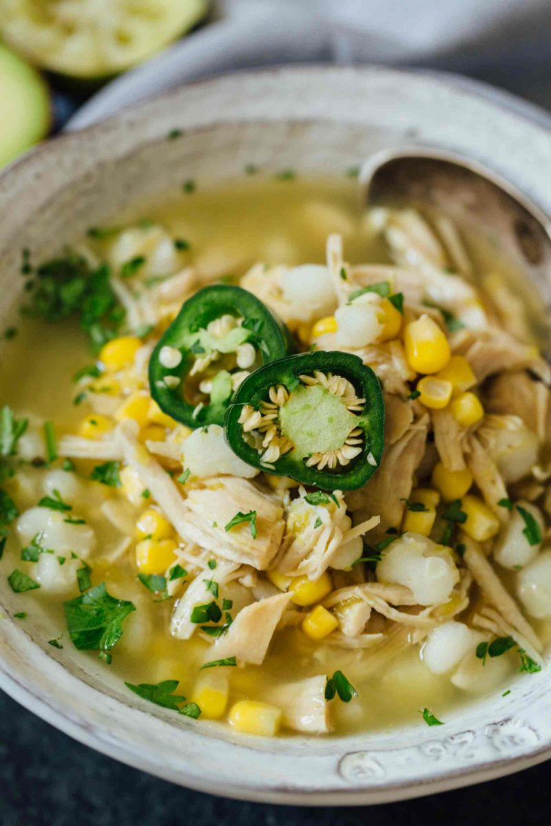 This Instant Pot jalapeño lime chicken soup is beyond flavorful! The spicy broth has hearty additions of hominy, corn, and shredded chicken. Put this all together in less than an hour!