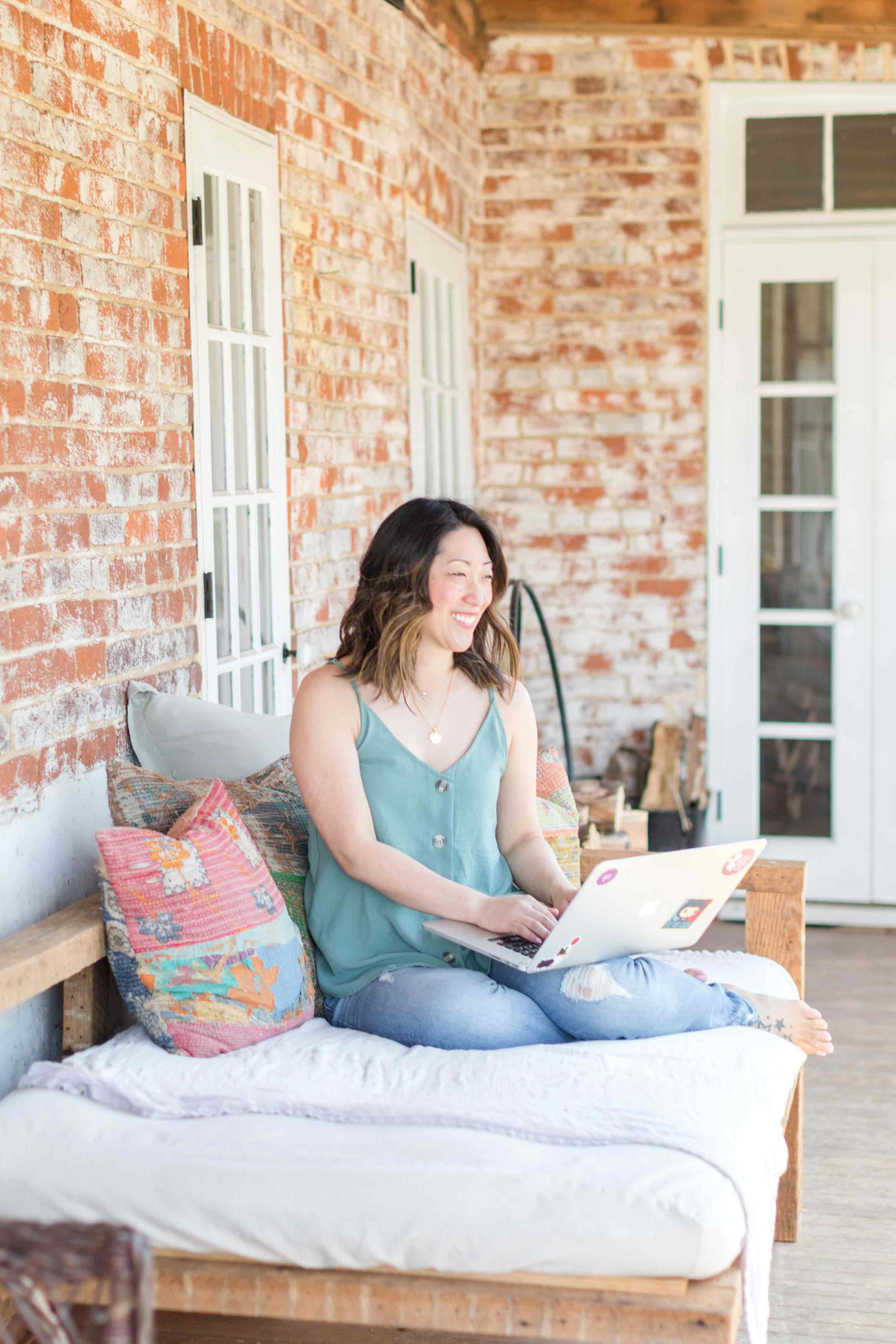 Julie Wampler on laptop on patio; photography by Anna Grace Photography