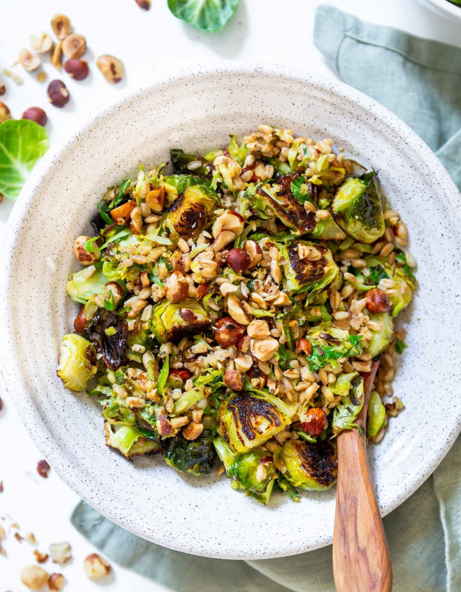 The perfect springtime salad! This warm roasted brussels sprouts salad with farro is tossed in a delicious Dijon shallot dressing that is flavorful and a delight! The hazelnuts give this salad that extra crunch and texture!