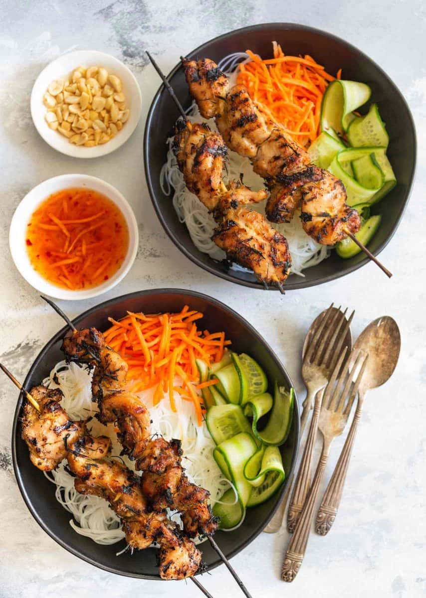 overhead shot of lemongrass chicken skewers with rice noodles