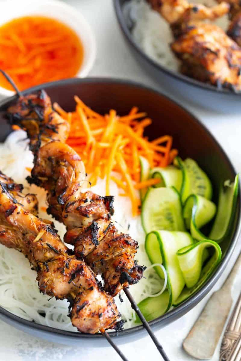 lemongrass chicken skewers on top of rice noodle bowl with veggies