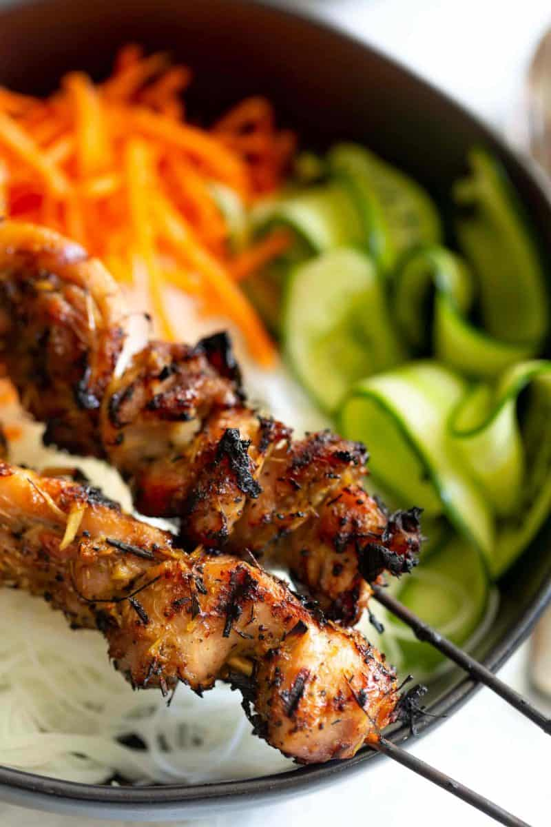 close up shot of lemongrass chicken skewers on top of rice noodle bowl with veggies