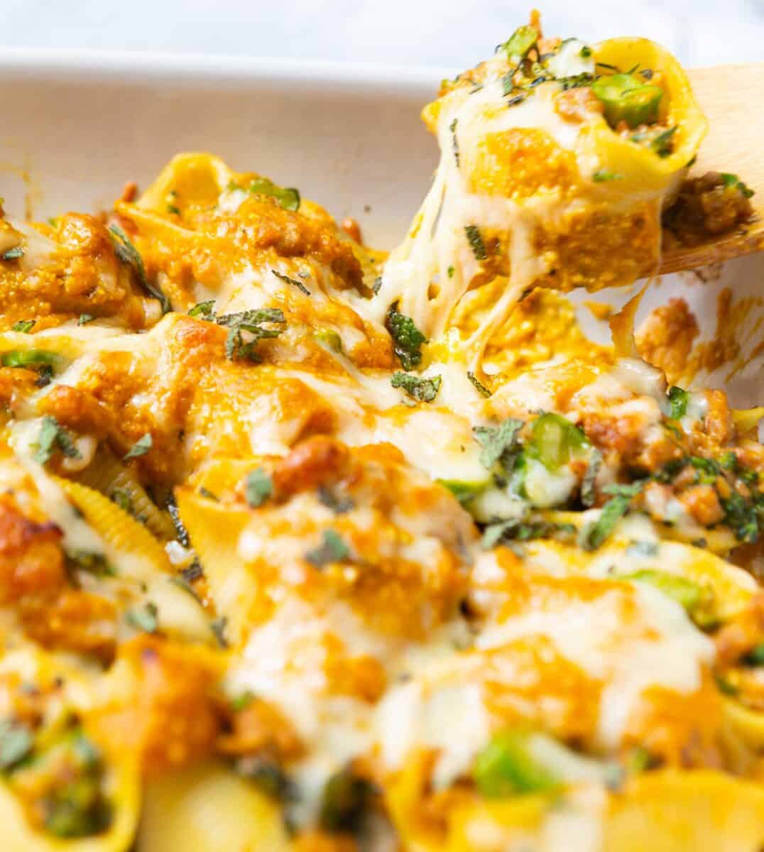 Filled with spicy sausage, broccolini, and a cheesy pumpkin sauce, this pumpkin stuffed shells recipe is the ultimate Fall comfort food!