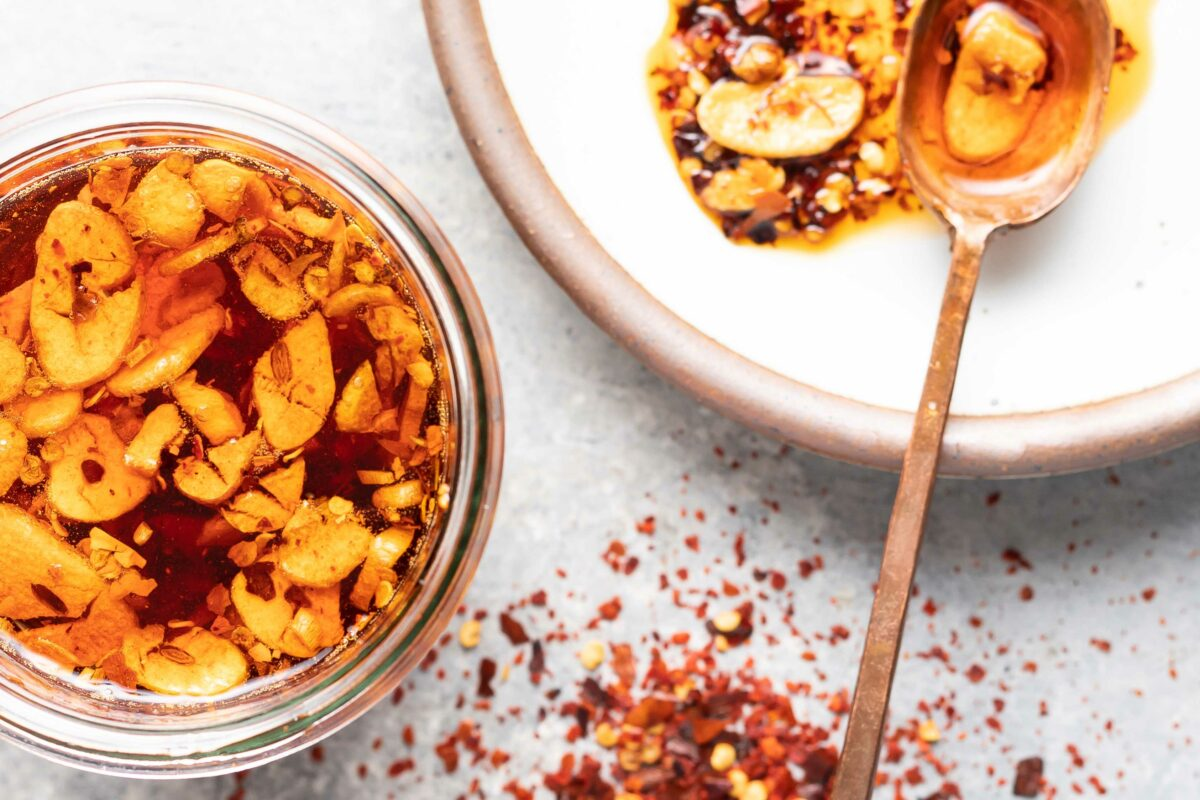 Red pepper flakes are dashed on a white surface, next to a white bowl and glass jar, both containing chili garlic oil.