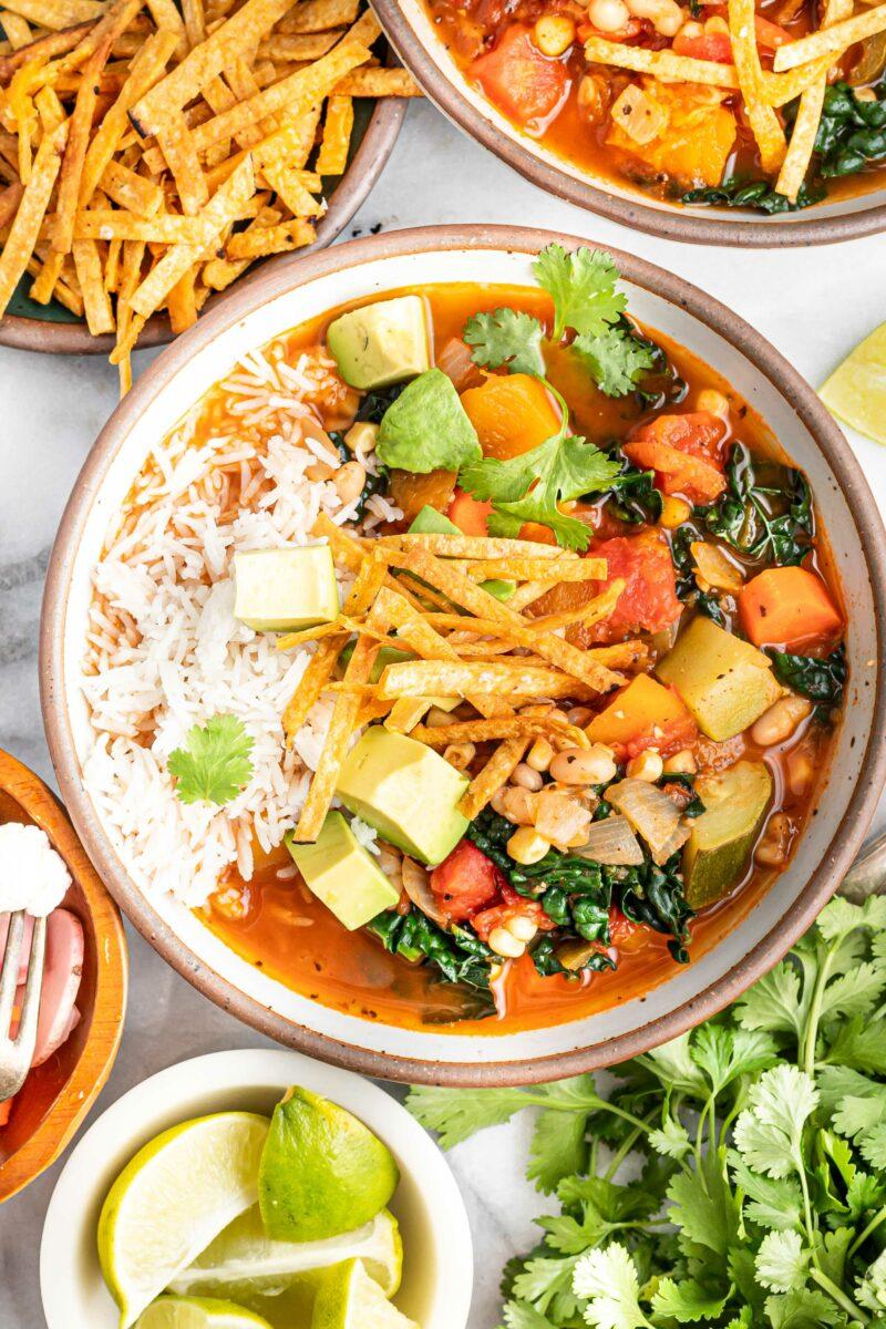 Freshly made tortilla strips, avocado and cilantro garnish a full bowl of Mexican vegetable and bean tortilla soup.