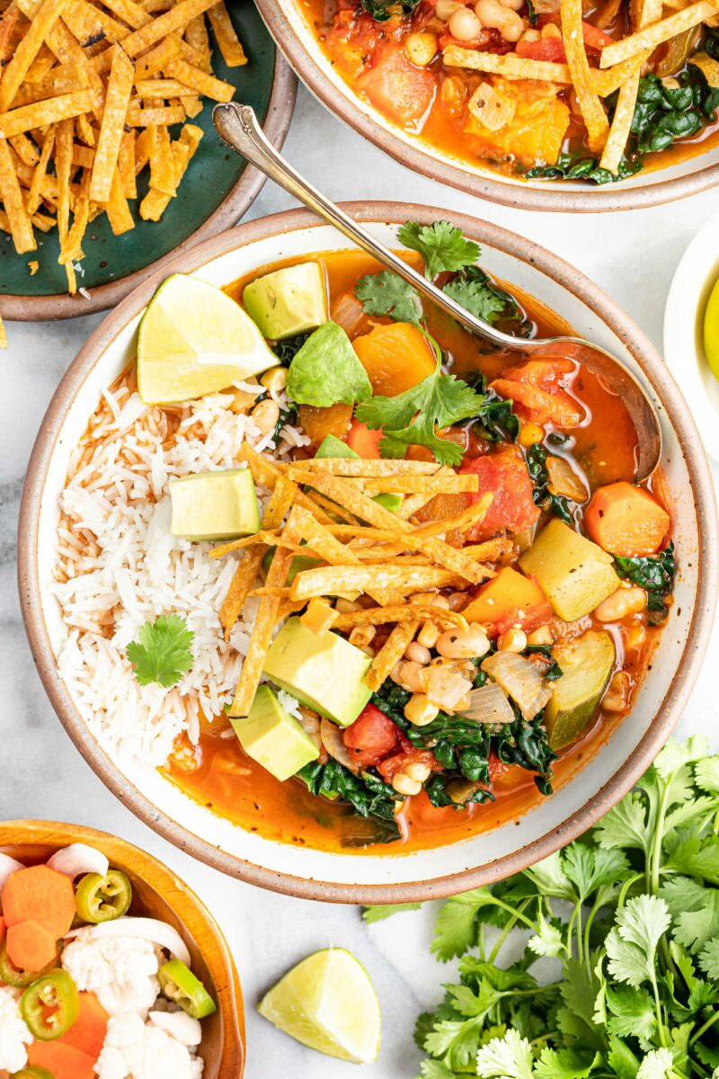 A spoon is sitting on the side of a bowl of Mexican vegetable and bean tortilla soup.