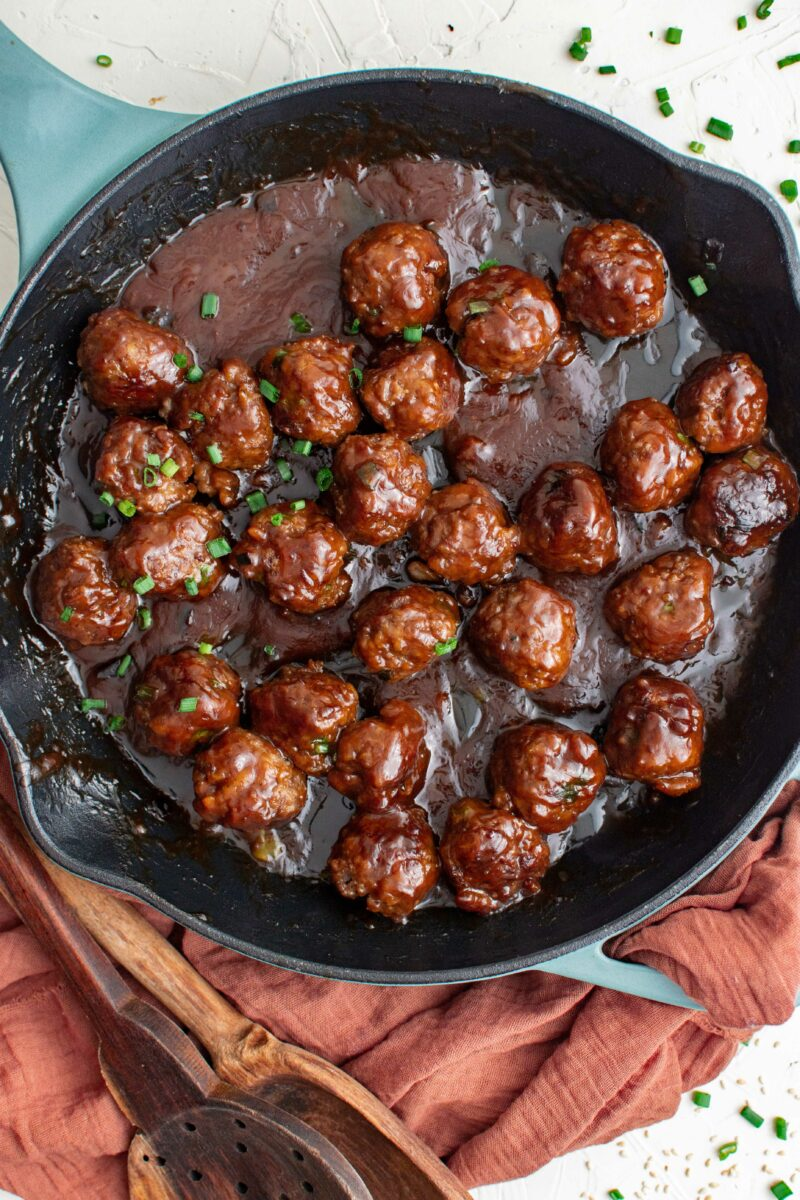 A large black skillet contains multiple cooked meatballs in a sticky dark brown sauce.