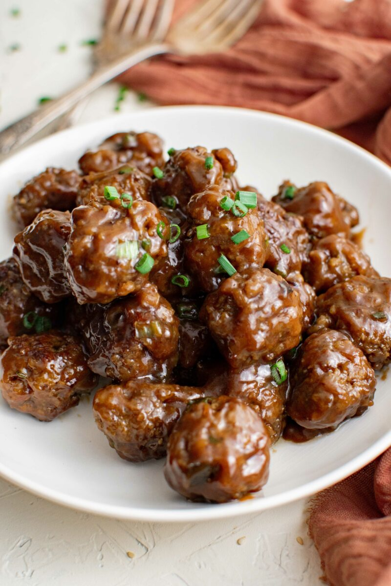 Meatballs are garnished with chopped green onions on a white plate.