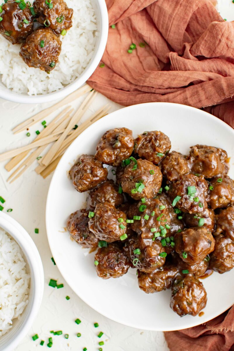 One large plate of garnished meatballs is placed next to serving picks and a small bowl of white rice and meatballs.