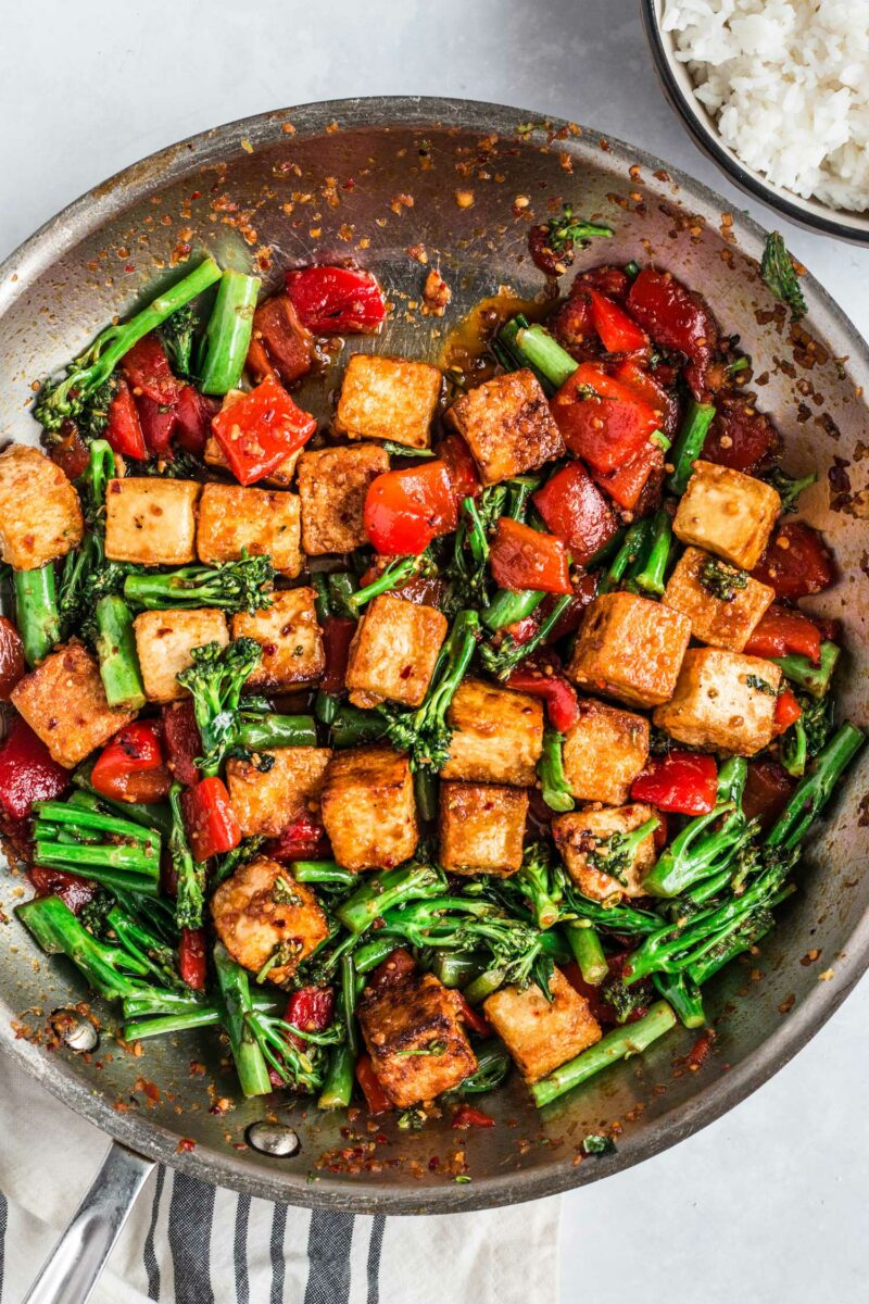 Spicy chili tofu stir fry is being cooked in a large skillet.