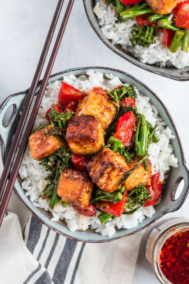 Two bowls of white rice and tofu stir fry are placed on a white surface and are ready to be eaten.