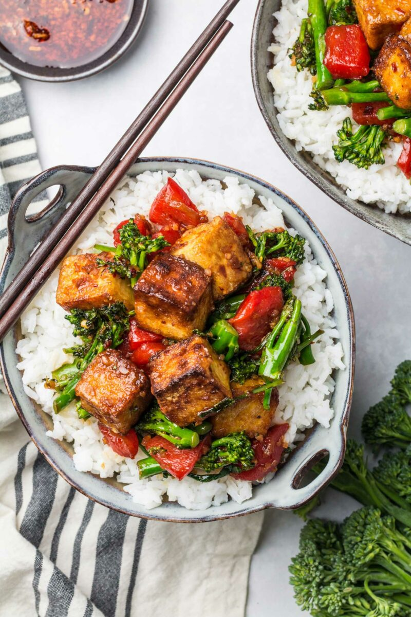 A serving of spicy tofu stir fry sits on a bed of white rice in a small bowl. Chopsticks sit on the side of the bowl.