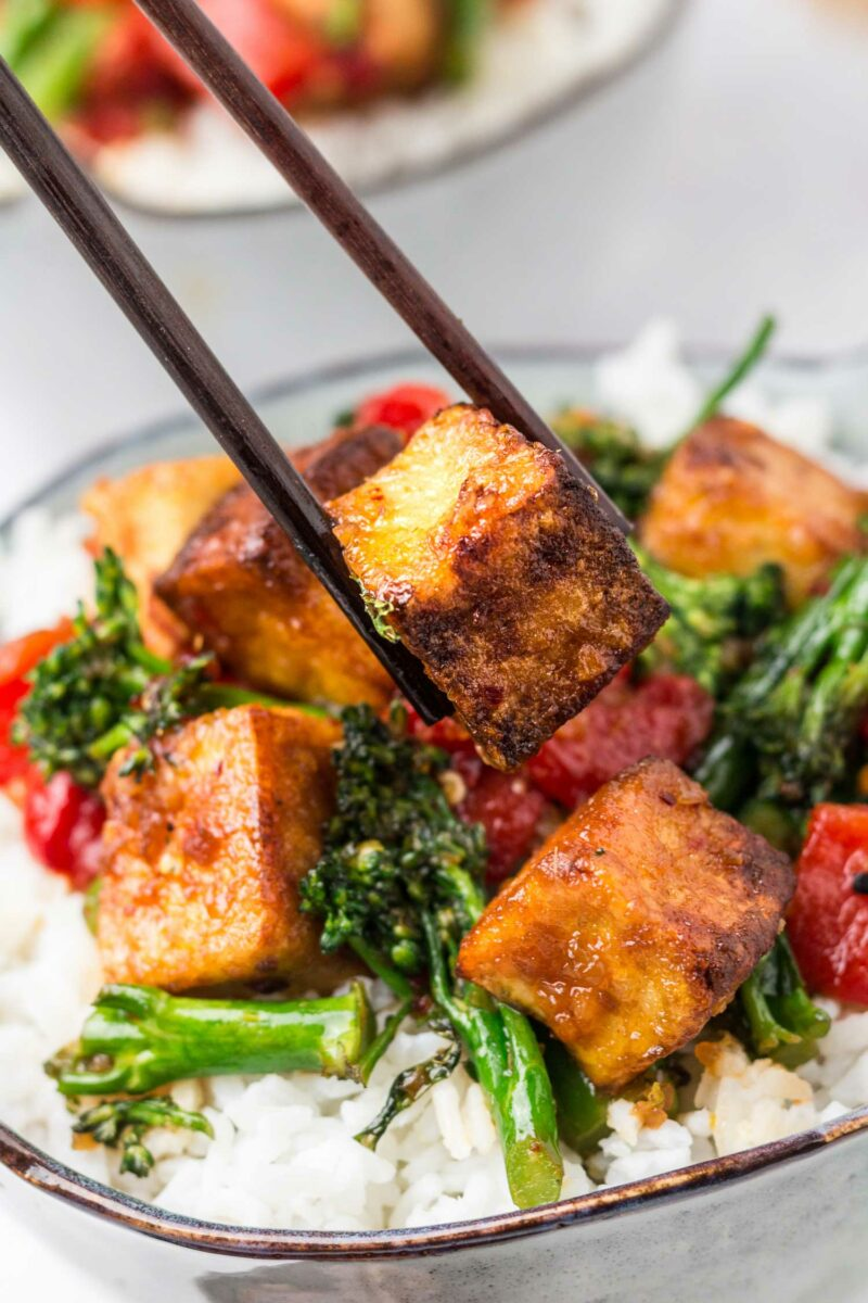 A piece of crispy tofu is being lifted from the bowl by a pair of dark brown chopsticks.