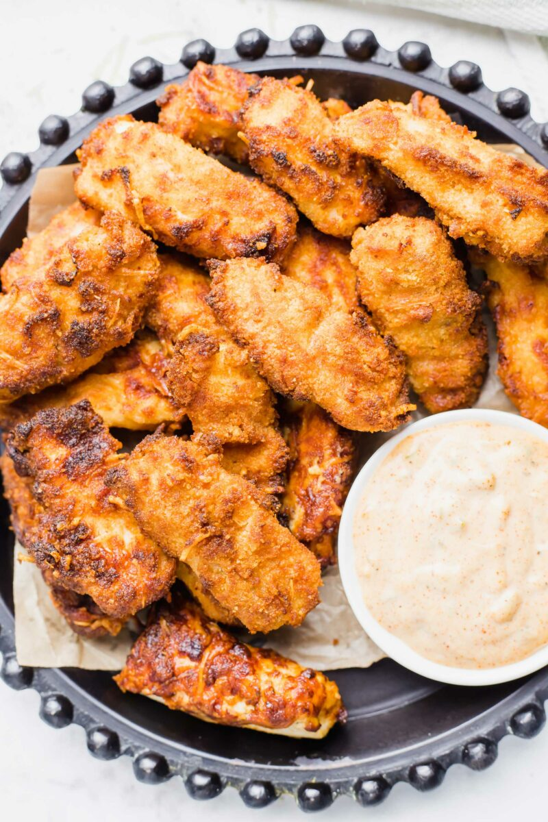 A number of crispy fish sticks are on a large serving platter with a small bowl of creamy cajun dipping sauce.
