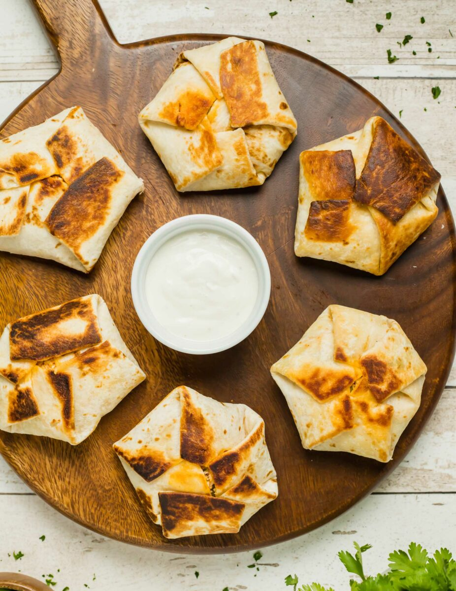 Six mini buffalo chicken crunchwraps are placed on a wooden serving platted with a small white bowl of dip in the middle.