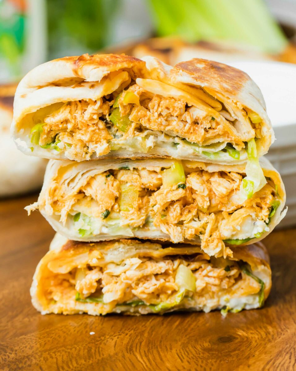 Three mini buffalo chicken appetizers have been cut in half and stacked in a little pile.