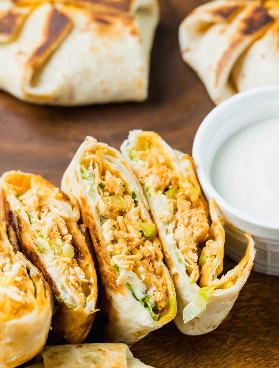 Mini chicken crunchwraps have been sliced in half and are placed on a brown surface next to a small white bowl of dip.