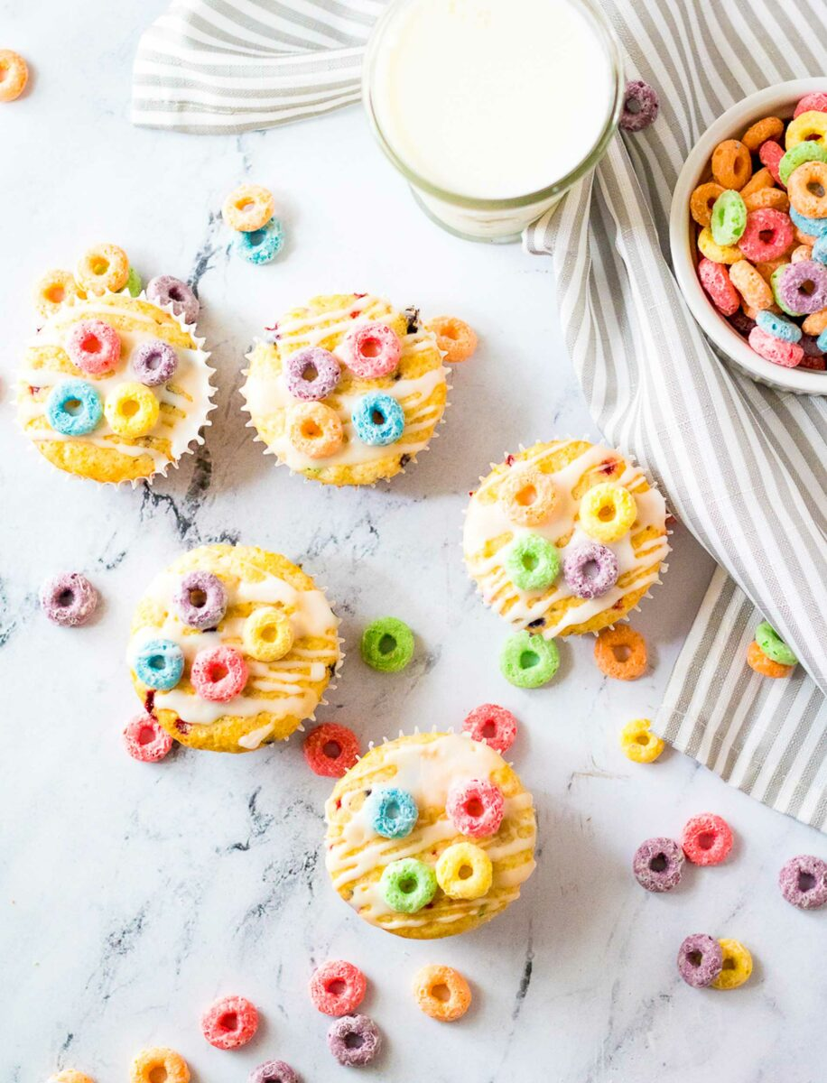 Five small cereal muffins are placed on a marble countertop, surrounded with pieces of fruity cereal.