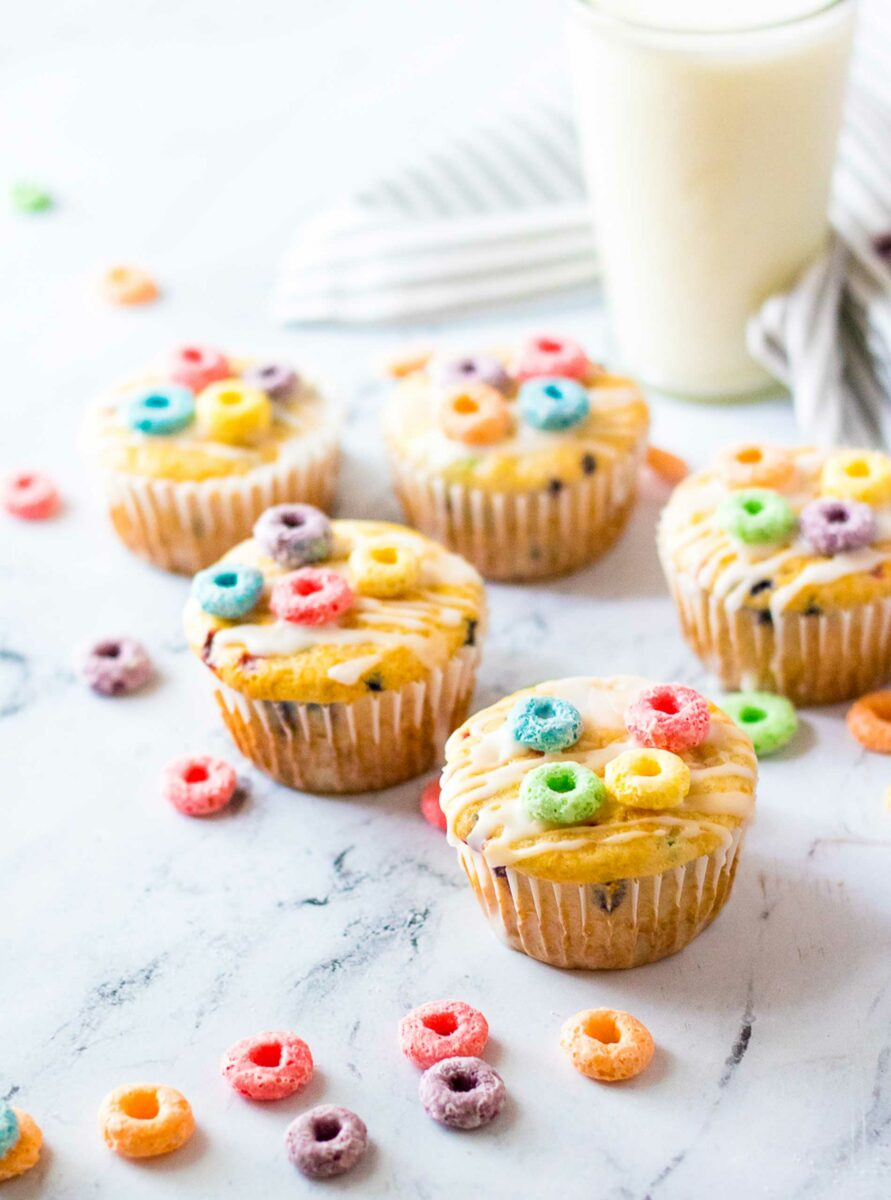 A glass of milk is in the background of several muffins on a white surface.