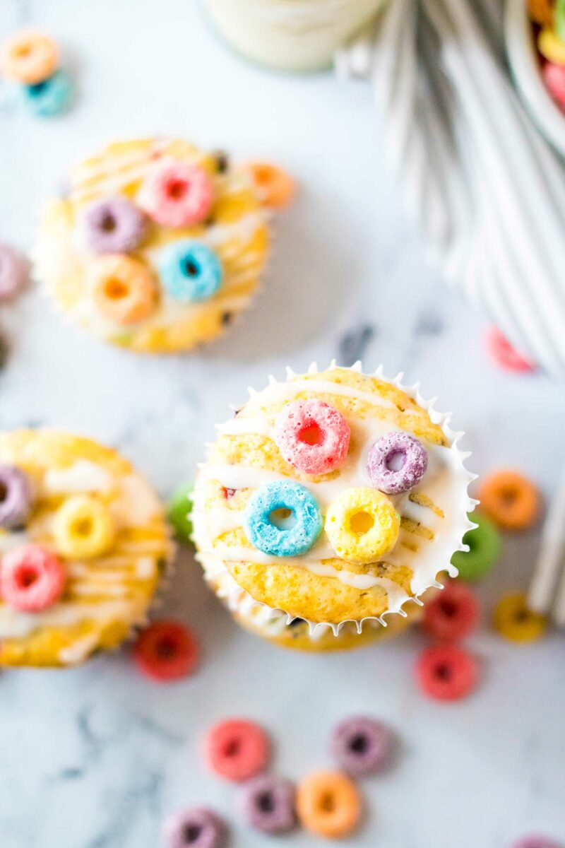 A close up shot shows a white drizzle over a muffin with four pieces of colorful cereal loops on top.