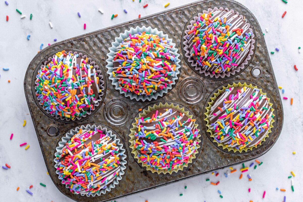 Six funfetti cocoa bombs are placed in a metal tray.