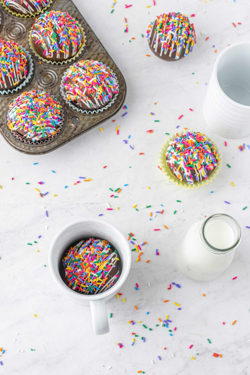 Sprinkles are spread out on a white countertop. A white mug contains a cocoa bomb next to a small jar of milk, across from a tray of more cocoa bombs.