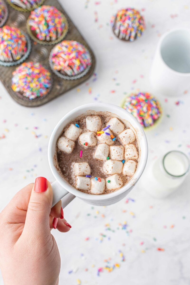 Marshmallows and sprinkles in a white mug are floating on top of hot cocoa.