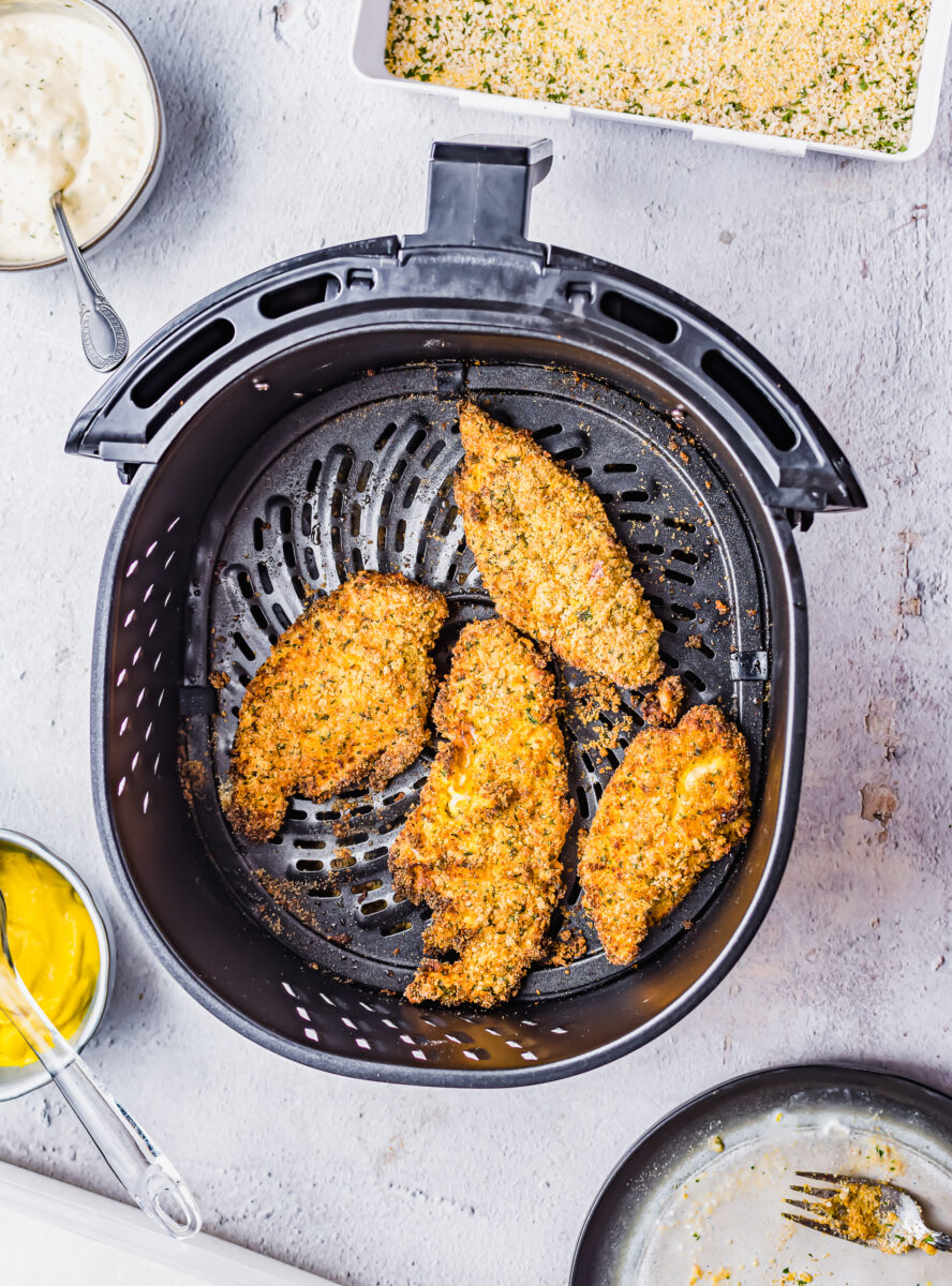 Four pieces of catfish are in the air fryer basket.