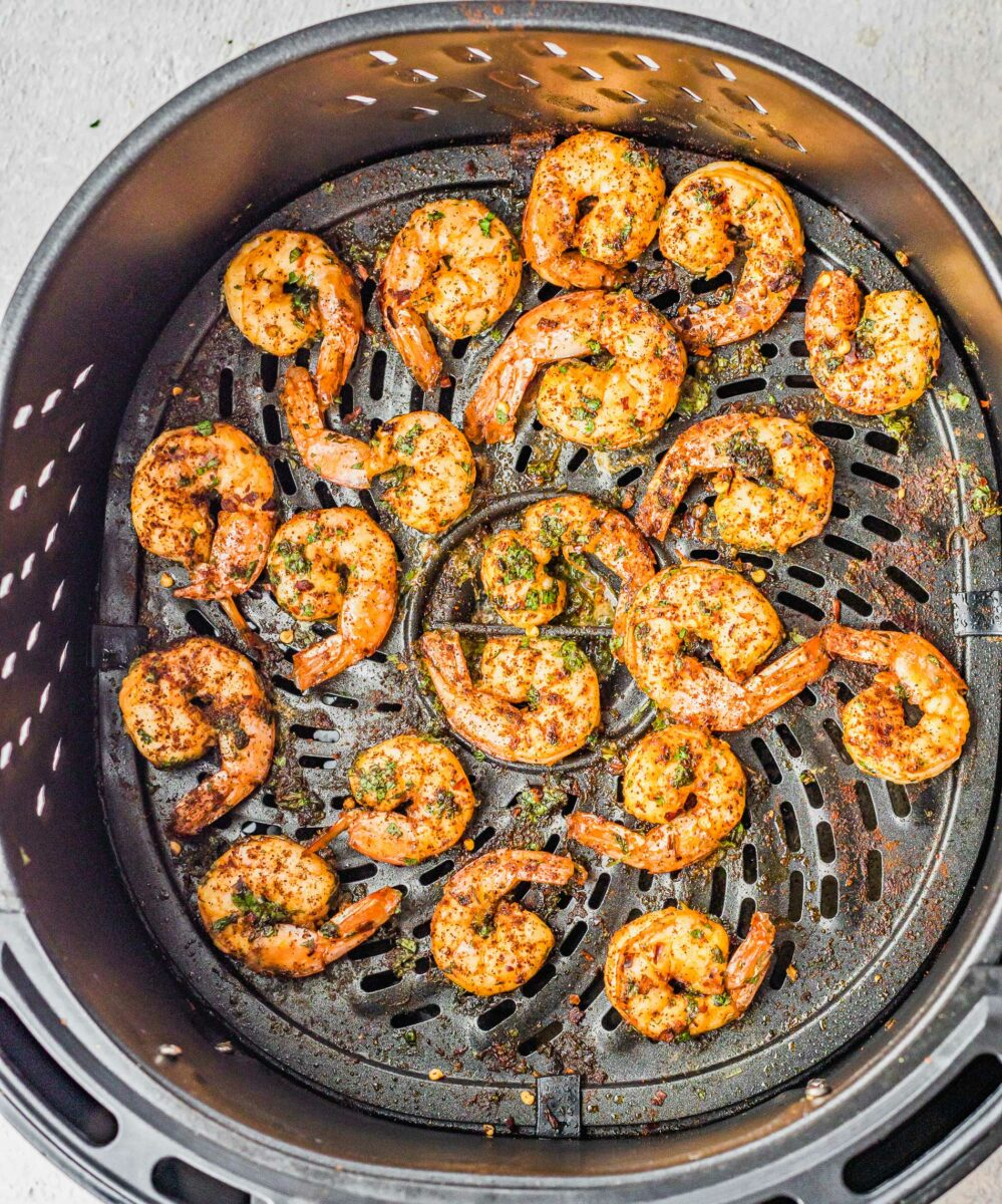 Shrimp are placed on the bottom of an air fryer basket.