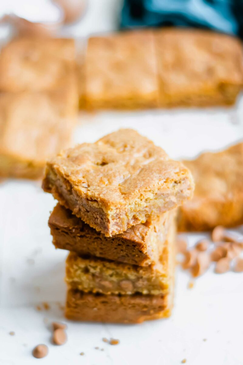 Four blondies are stacked on top of one another on a white surface.