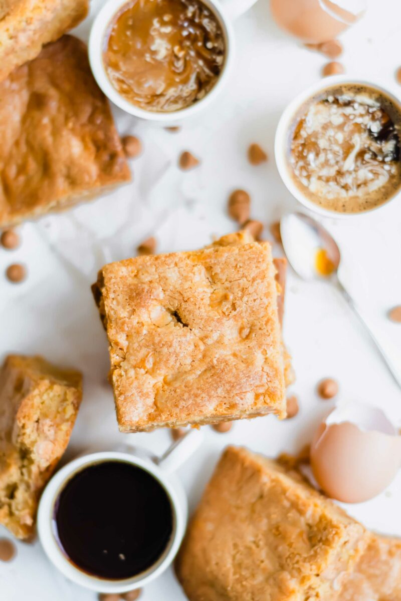 Three cups of coffee are placed next to a few pieces of blondies.