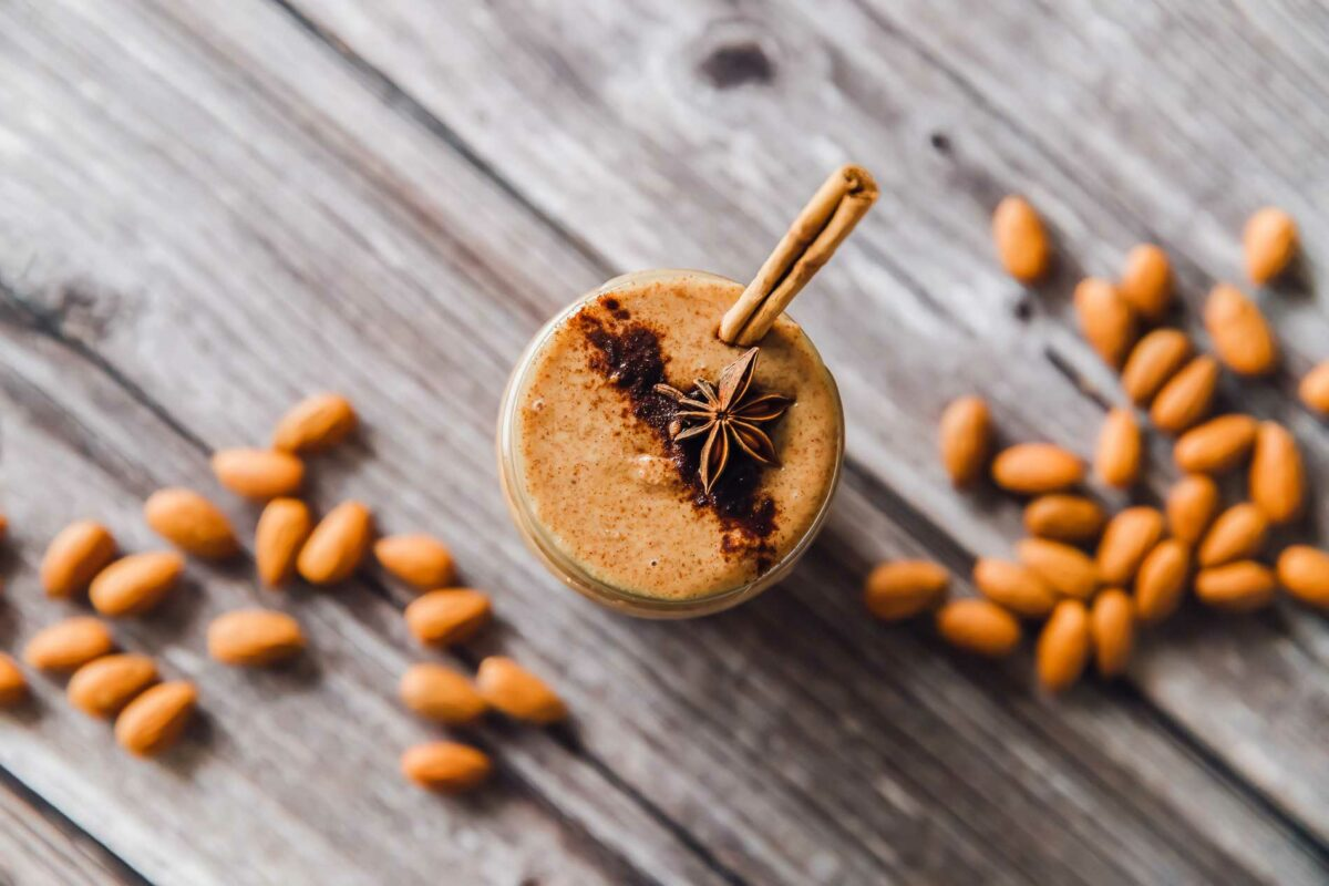 A jar of cinnamon almond butter is presented on a wooden surface and is surrounded by almonds.