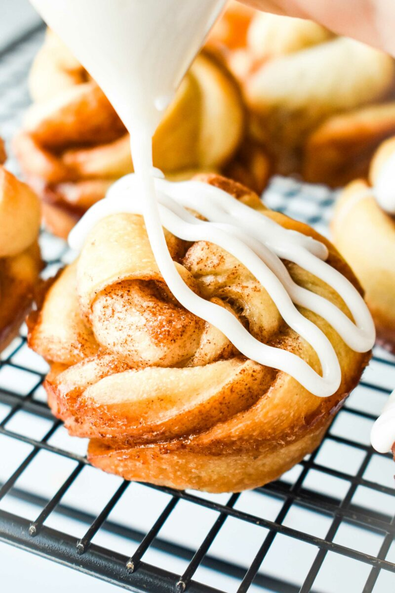 Vanilla icing is being drizzled on to a cinnamon twist muffin.