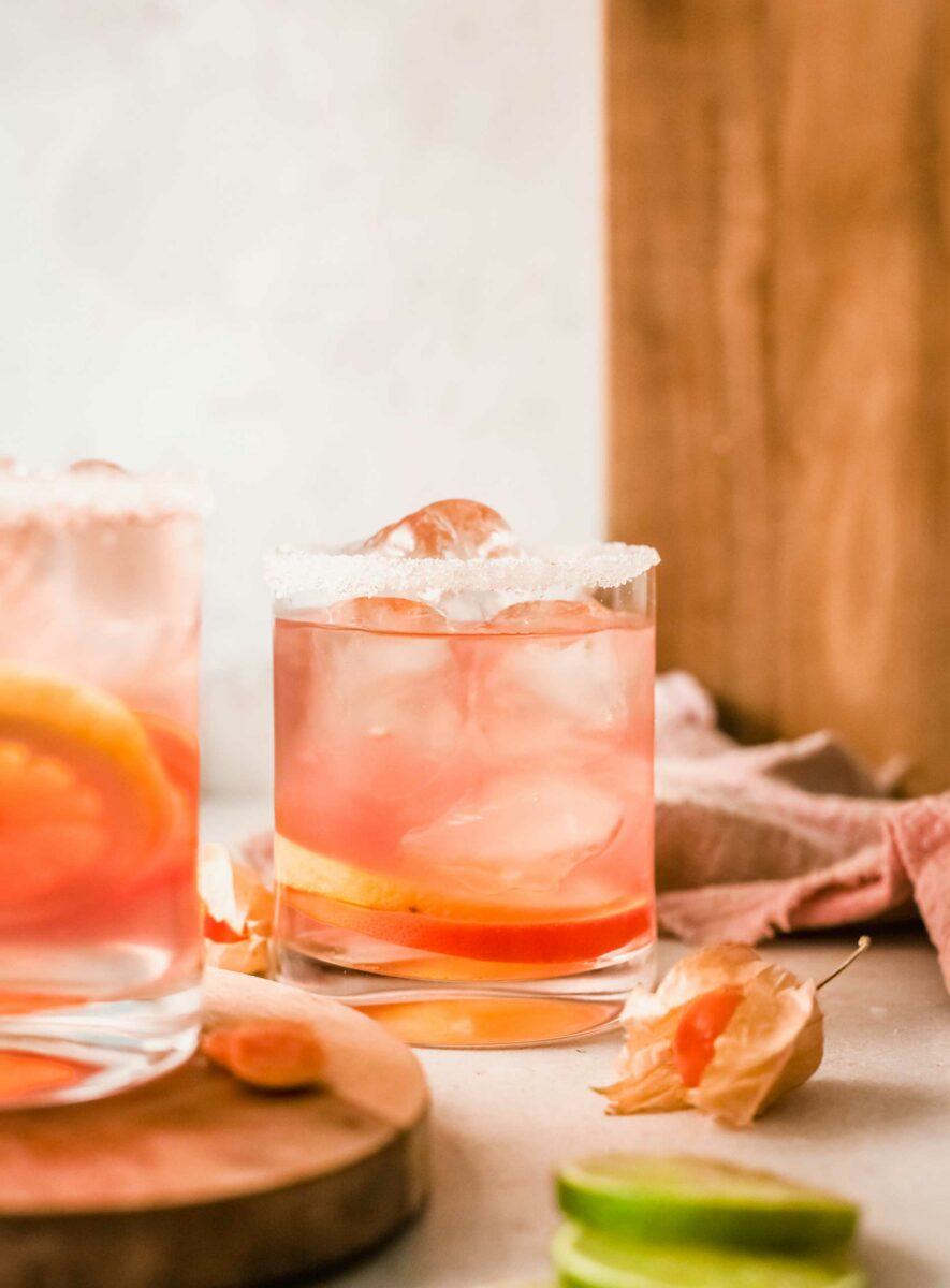 A glass of citrus rosé sangria is rimmed with sugar and filled with ice cubes.