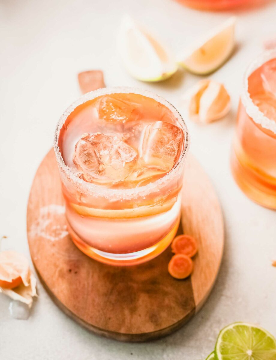 A glass of citrus rosé sangria is placed on a wooden surface.