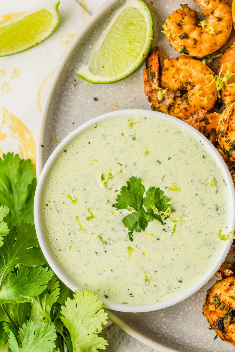 Grilled shrimp are placed next to a bowl of creamy cilantro dressing.