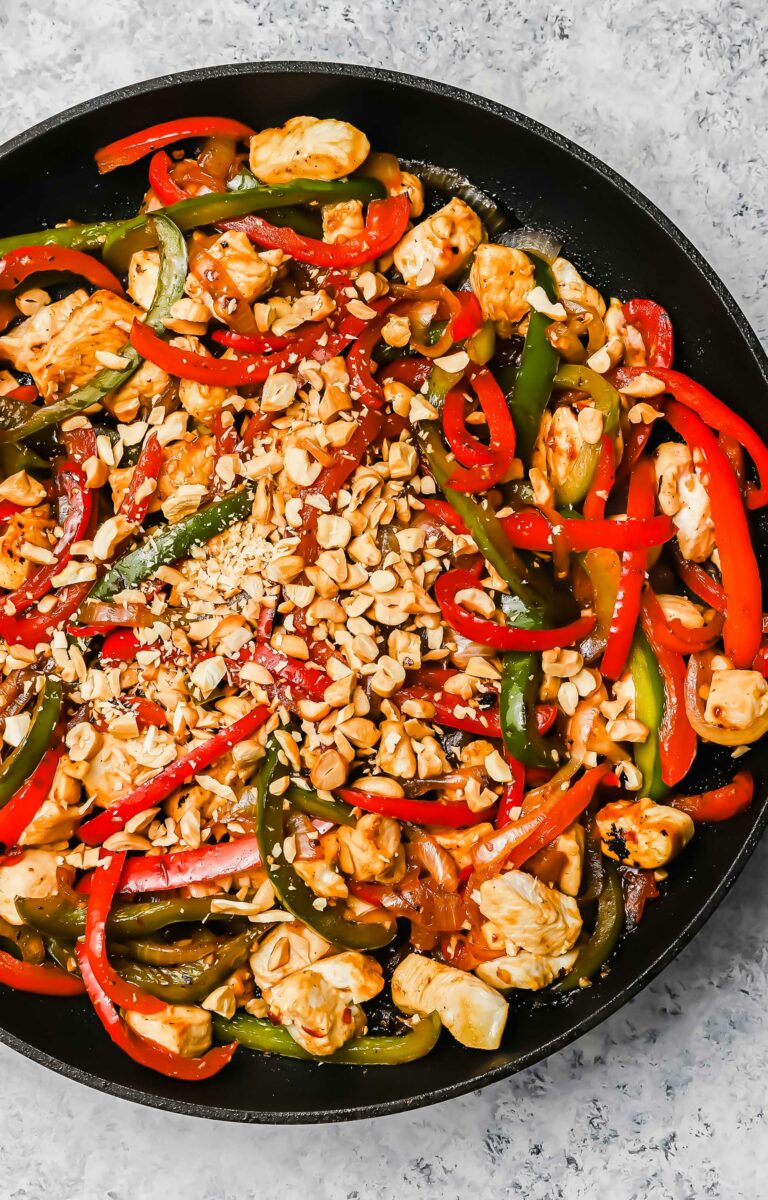 Roasted peanuts sit on top of freshly made Kung Pao chicken in a black skillet.