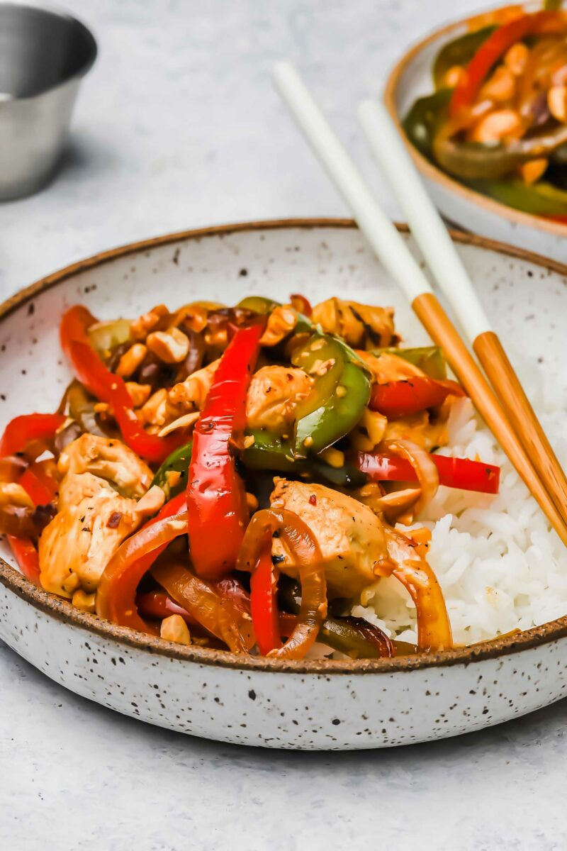 A small bowl of white rice and Kung Pao chicken is ready to be eaten with chopsticks.