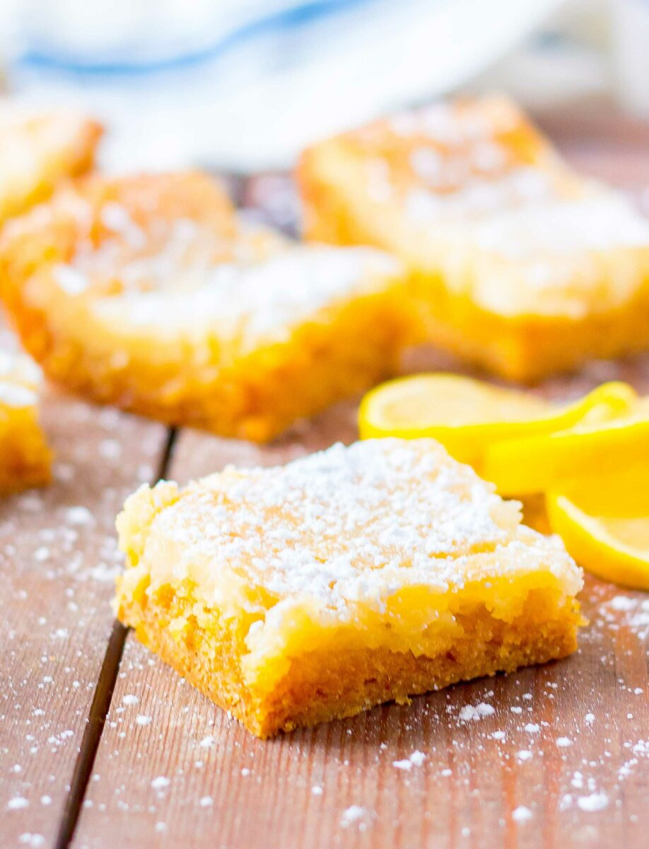 A few slices of lemon are placed next to a piece of gooey lemon cake.