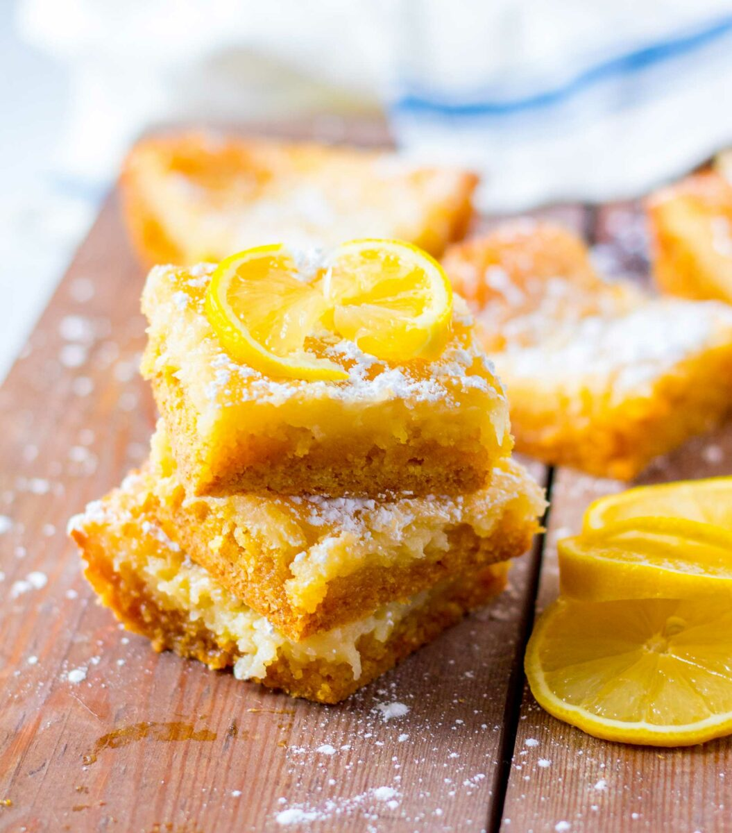 A few pieces of lemon cake are stacked on top of one another on a wooden surface.
