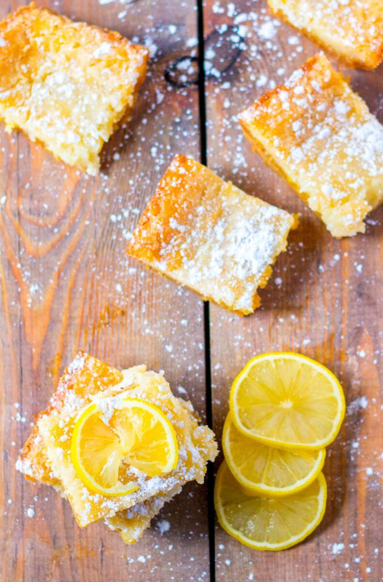 A lemon slice garnishes a square slice of lemon cake.